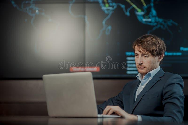 Jeunes il homme d'affaires d'ing?nieur avec l'ordinateur portable en aluminium moderne mince dans la chambre de serveur de r?seau photographie stock