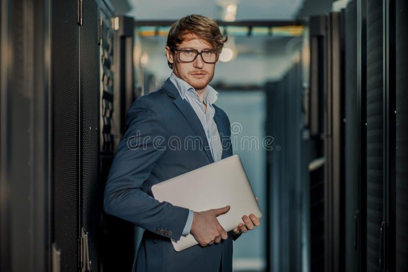 Jeunes il homme d'affaires d'ing?nieur avec l'ordinateur portable en aluminium moderne mince dans la chambre de serveur de r?seau image stock