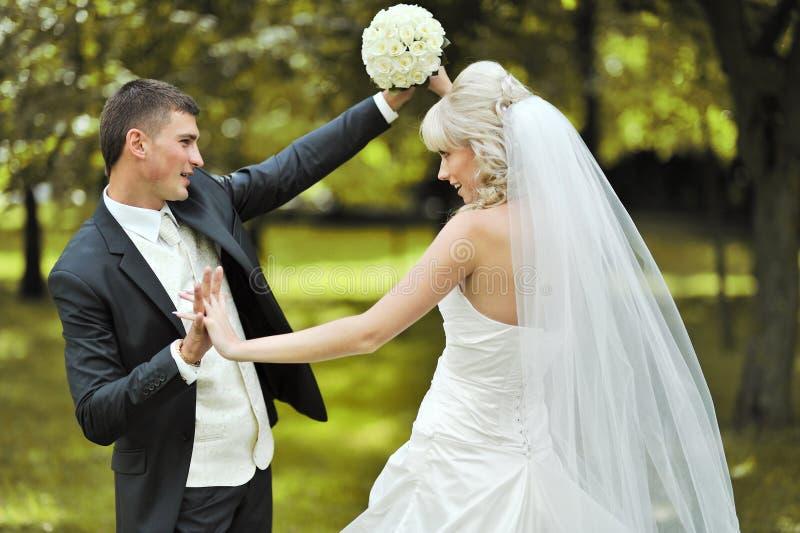 Jeunes jeunes mariés heureux nous dansant ensemble à l'extérieur sur le leur photographie stock libre de droits
