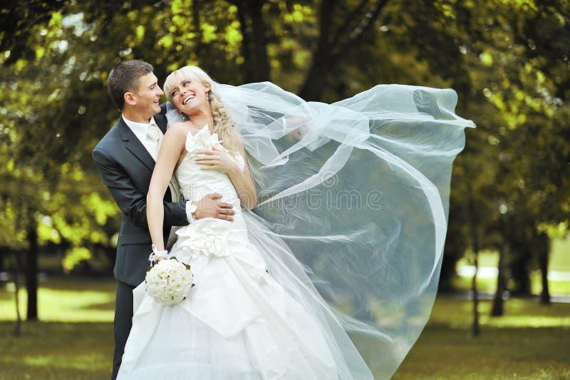 Jeunes jeunes mariés heureux riant et s'étreignant sur t images stock