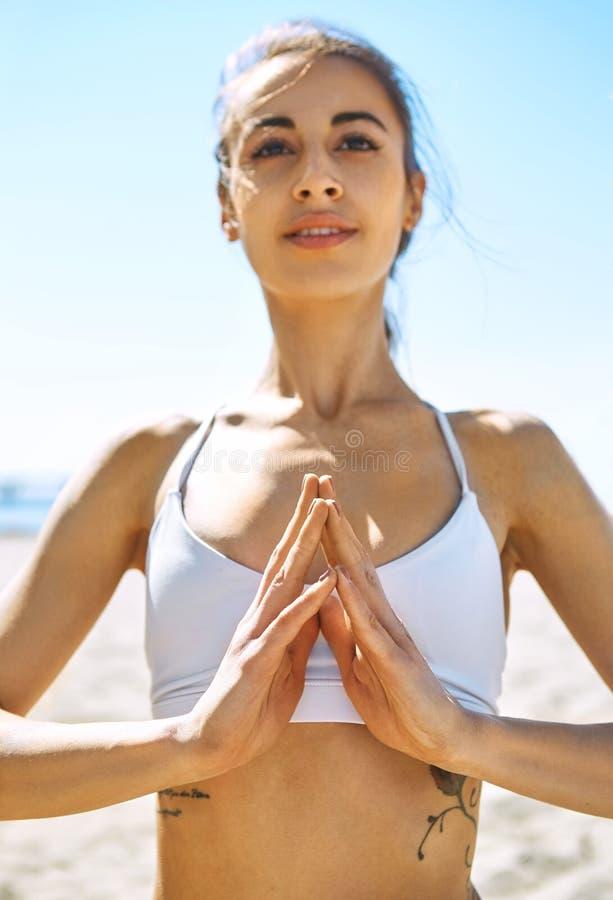 Jeunes jolis yoga et méditation de pratique de détente de sourire de femme sur la plage de sable au jour d'été ensoleillé chaud photos stock