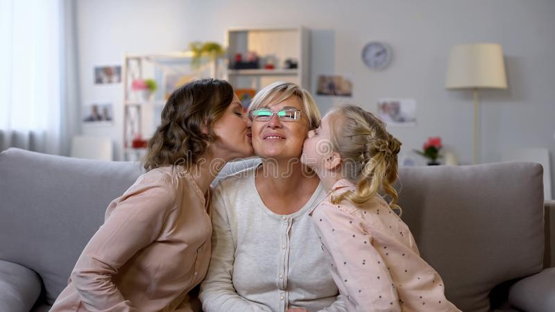 Jeunes joues de baiser de grand-m?re de femelle et d'enfant, ?treignant ensemble, amour de famille photos libres de droits