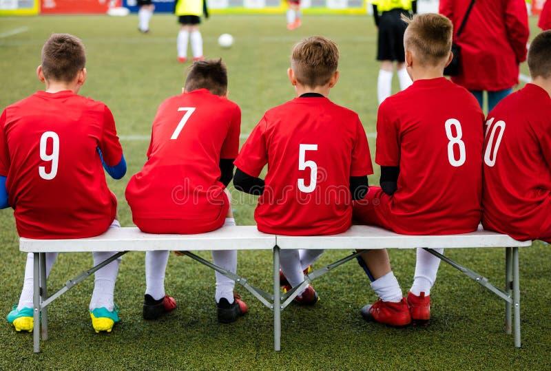 Jeunes joueurs de football Le jeune football Team Sitting sur le banc en bois Match de football pour des enfants Young Boys jouan photo stock