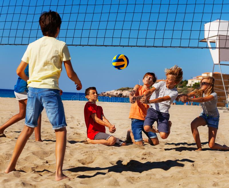 Jeunes joueurs de volleyball dans l'action sur la cour de sable photographie stock libre de droits