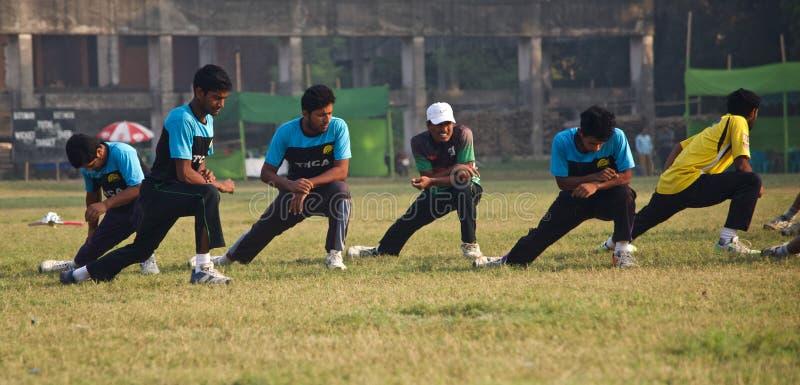 Jeunes joueurs s'étirant autour d'un au sol de cricket photo libre de droits