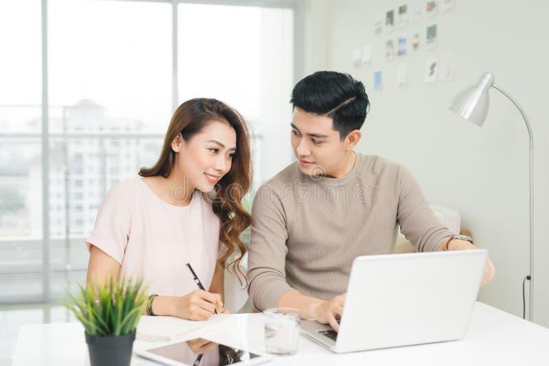 Jeunes lecture heureuse de couples et factures d'analyse se reposant à la table photographie stock