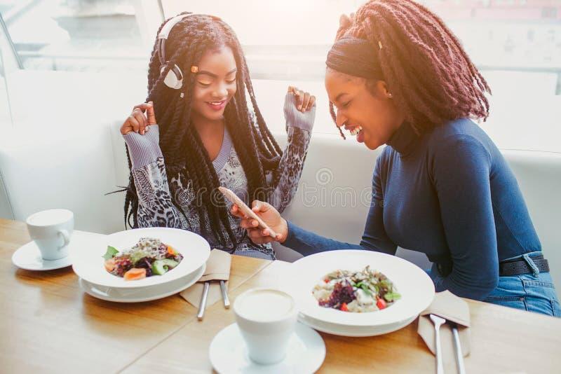 Jeunes les femmes africaines heureuses et positives ont l'amusement Premier modèle écouter la musique En second lieu sourires Ils photographie stock libre de droits