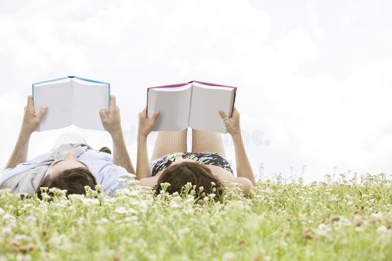 Jeunes livres de lecture décontractés de couples tout en se trouvant sur l'herbe contre le ciel image stock