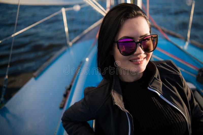 Jeunes lunettes de soleil de port de sourire de brune se reposant sur un panneau de bateau dans le jour ensoleillé d'automne, mar photo libre de droits