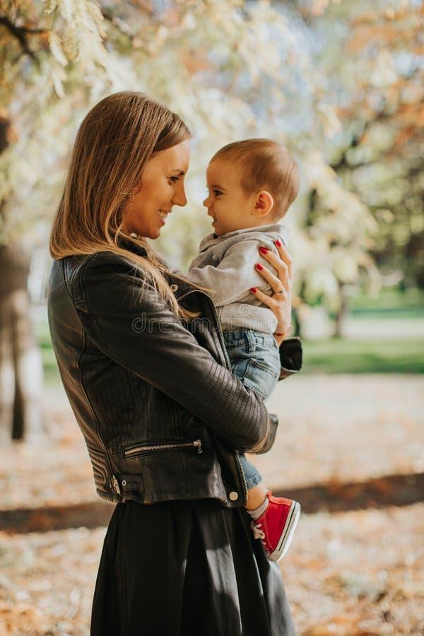 Jeunes mère et bébé garçon en parc d'automne image stock
