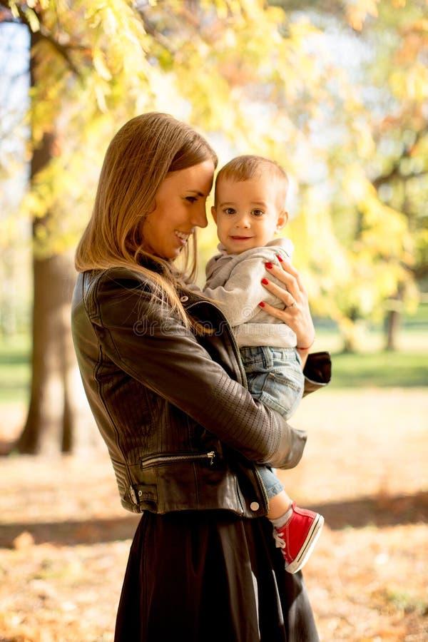 Jeunes mère et bébé garçon en parc d'automne photo stock