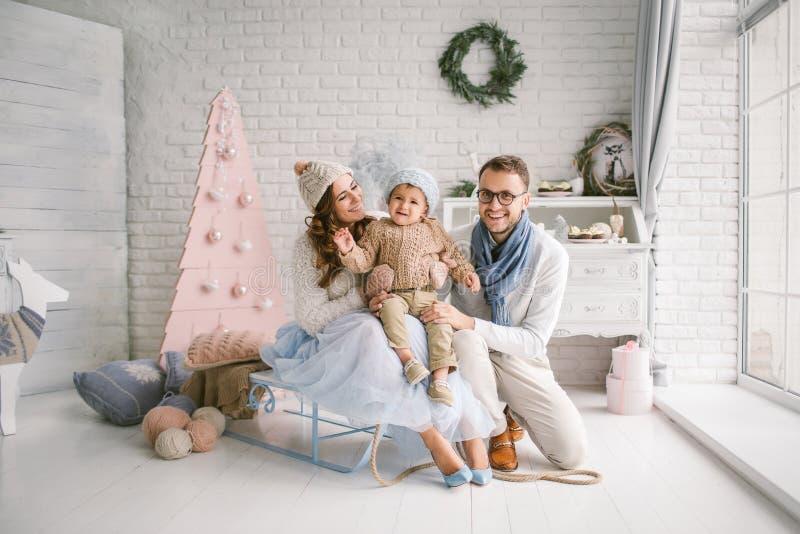 Jeunes mère et bébé garçon heureux de père dans le studio de Noël photographie stock