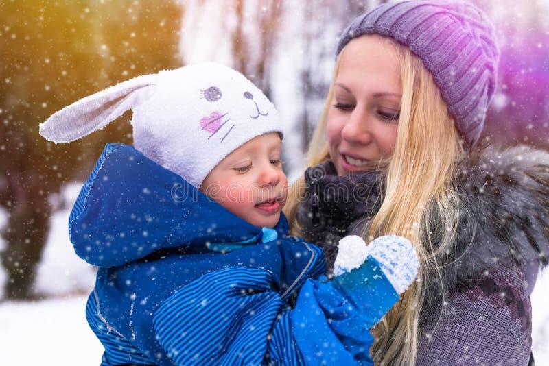 Jeunes mère heureuse et bébé jouant dans le froid photos libres de droits