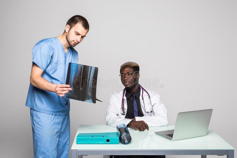 Jeunes médecins discutant le diagnostic dans le bureau lumineux Deux médecins disscusing le rayon X à la table de bureau d'isolem photos stock