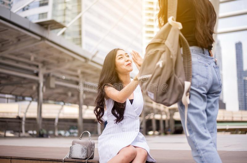 Jeunes mains asiatiques de femme se réunissant, salutation heureuse de l'ami deux dans la rue image stock