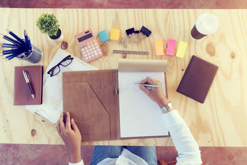 Jeunes mains de travailleuse active d'affaires montrant le rapport et extorquer un carnet sur la table en bois substance avec le  image stock