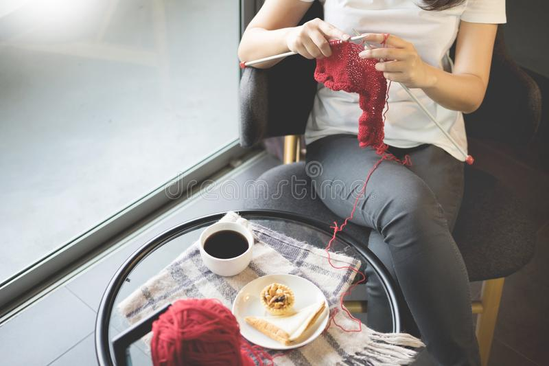 Jeunes mains de woman's tricotant les chandails chauds Se reposant sur le vieux fauteuil près de la fenêtre, concept de détente photographie stock