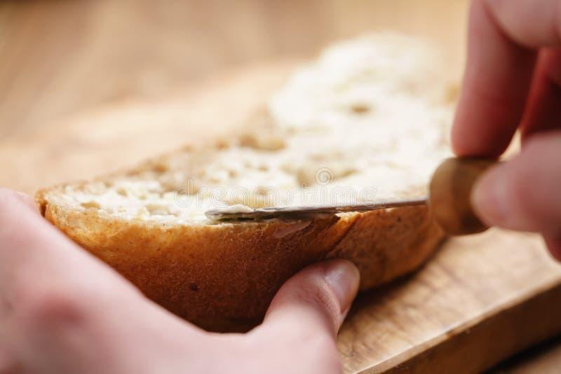 Jeunes mains femelles répandant le beurre sur le pain photo stock