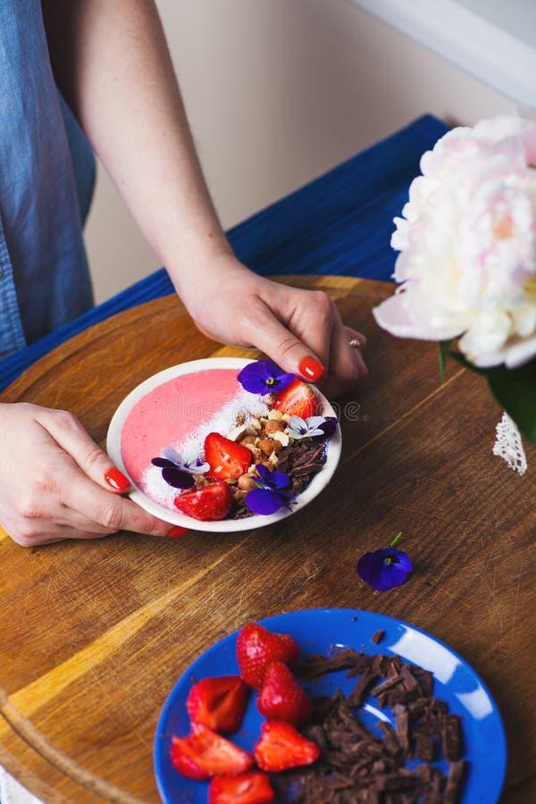 Jeunes mains femelles tenant le bol rose de smoothie avec la fraise, écrous, chocolat et décoré des fleurs, courbes photos libres de droits