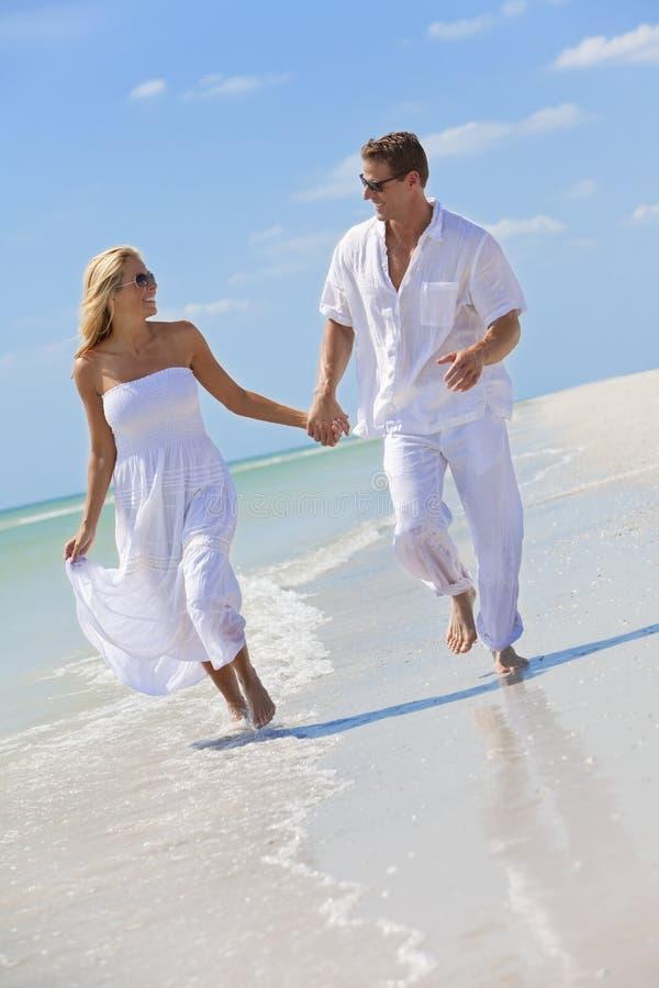 Jeunes mains heureuses de fixation de couples sur une plage photo libre de droits