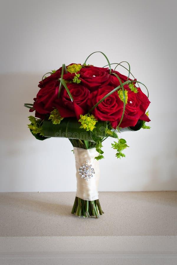 Jeunes mariées épousant le bouquet des roses rouges image stock
