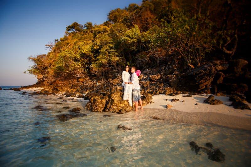 Jeunes mariés à la plage contre des roches au lever de soleil photos stock