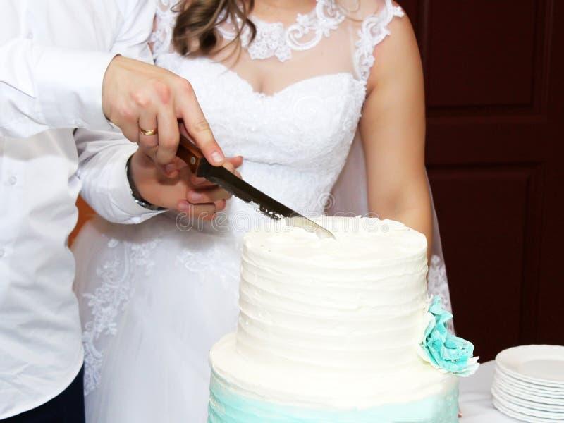 Jeunes mariés à la réception de mariage coupant le gâteau de mariage photos stock