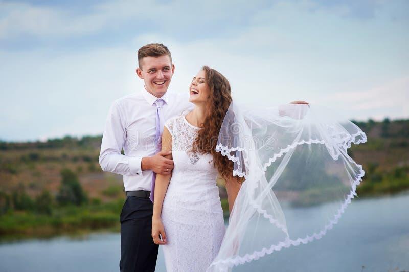 Jeunes mariés affectueux marchant sur un fond de lac images libres de droits