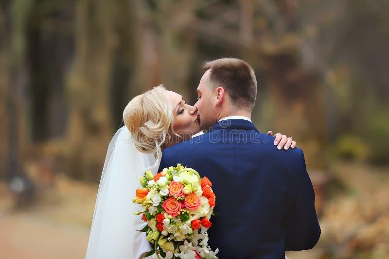 Jeunes mariés au jour du mariage marchant dehors sur la nature de ressort image libre de droits