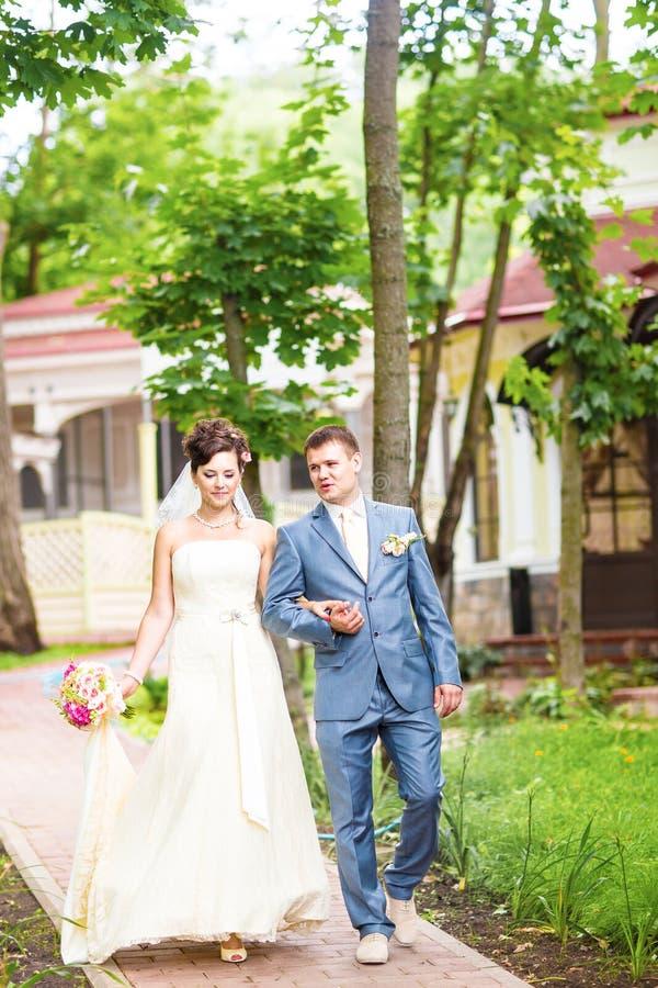 Jeunes mariés au jour du mariage marchant dehors sur la nature de ressort Couples nuptiales, femme heureuse de nouveaux mariés et photographie stock