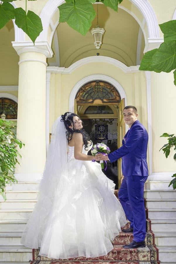 Jeunes mariés avec un bouquet des fleurs sur les escaliers images stock