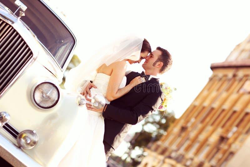Jeunes mariés avec une rétro voiture blanche image libre de droits