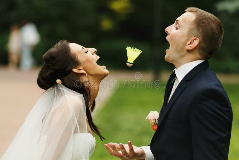 Jeunes mariés ayant l'amusement essayant d'attraper avec leurs mouthes a images libres de droits