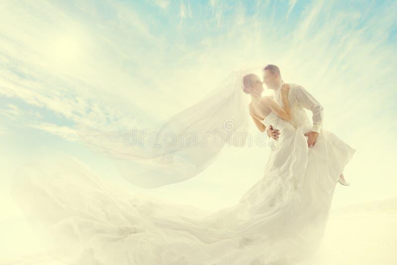 Jeunes mariés Couple Dancing, robe de mariage et long voile photographie stock
