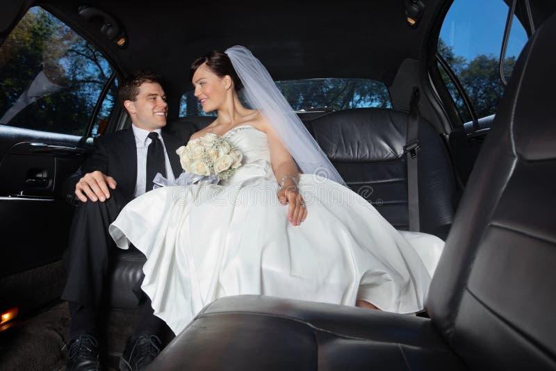 Jeunes mariés dans la limousine images libres de droits
