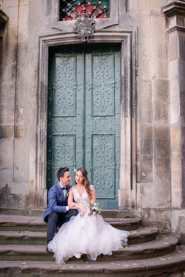 Jeunes mariés dans le repos bleu de costume sur les vieux pas en pierre photos stock