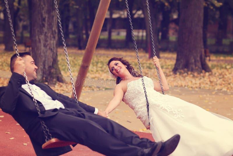 Jeunes mariés dans une oscillation image stock