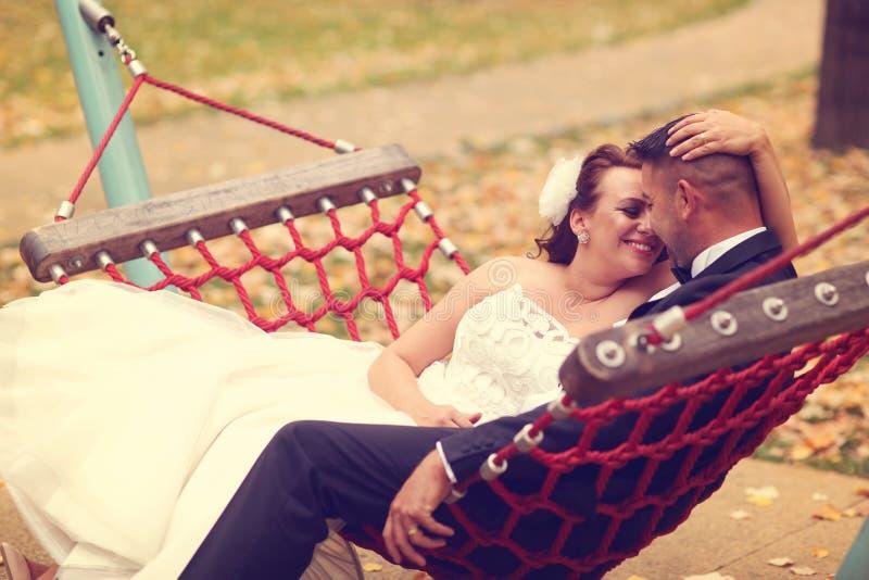 Jeunes mariés dans une oscillation photographie stock libre de droits