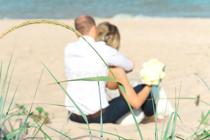 Jeunes mariés de Blured au coucher du soleil sur une belle plage, ménage marié romantique photos stock