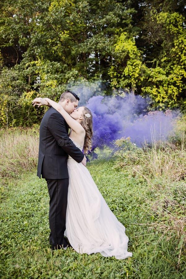 Jeunes mariés embrassant dans la forêt avec de la fumée pourpre photographie stock