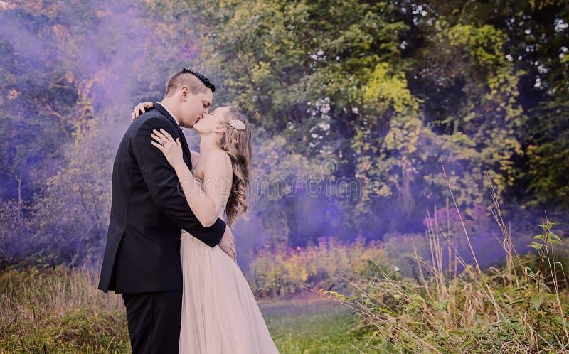 Jeunes mariés embrassant dans la forêt avec de la fumée pourpre image stock
