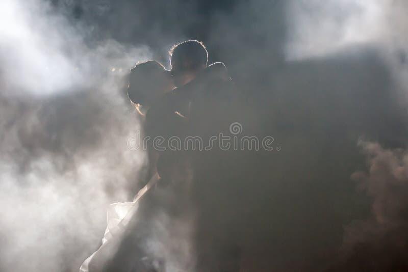 Jeunes mariés embrassant en brouillard la nuit image stock