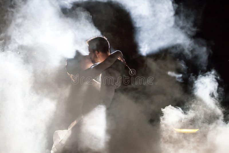 Jeunes mariés embrassant en brouillard la nuit photo stock