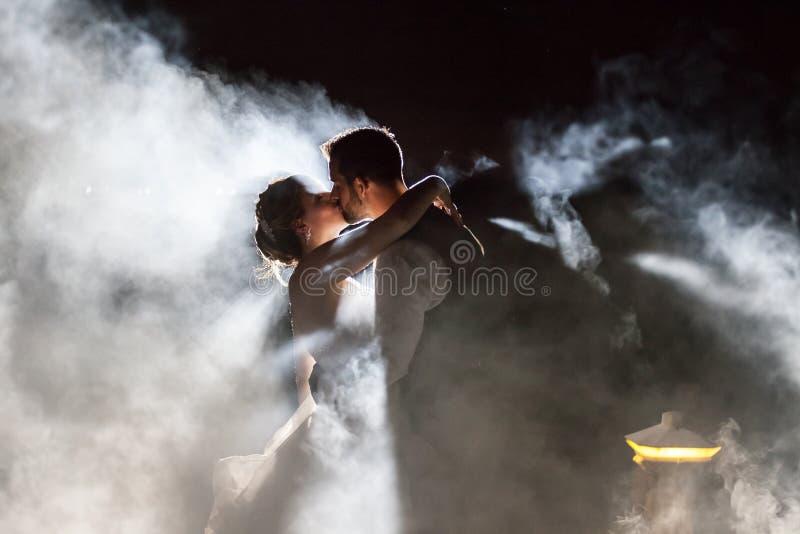 Jeunes mariés embrassant en brouillard la nuit images stock