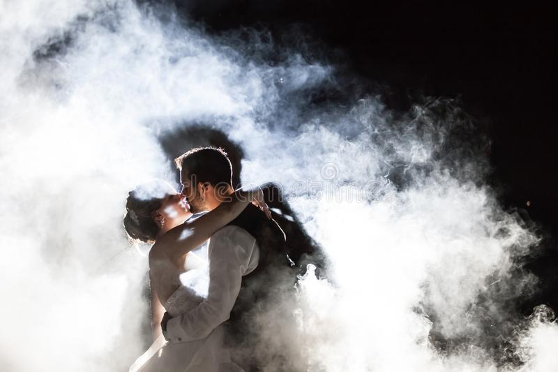 Jeunes mariés embrassant en brouillard la nuit images libres de droits