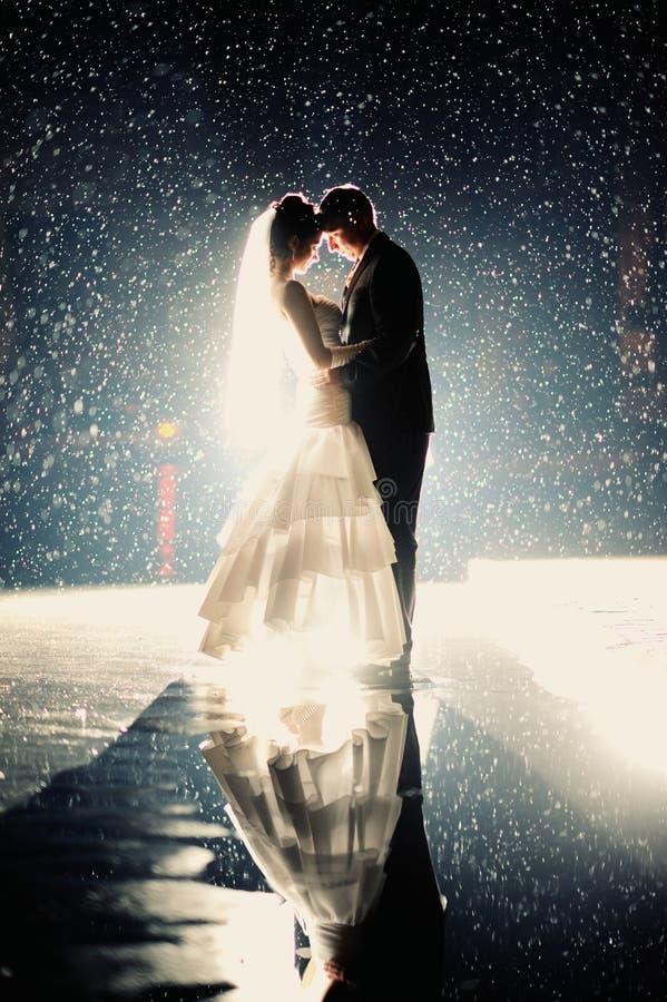 Jeunes mariés embrassant sous la pluie photo libre de droits