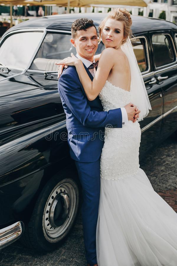 Jeunes mariés heureux élégants embrassant à la vieille rétro voiture noire Couples les épousant magnifiques des nouveaux mariés é photo libre de droits
