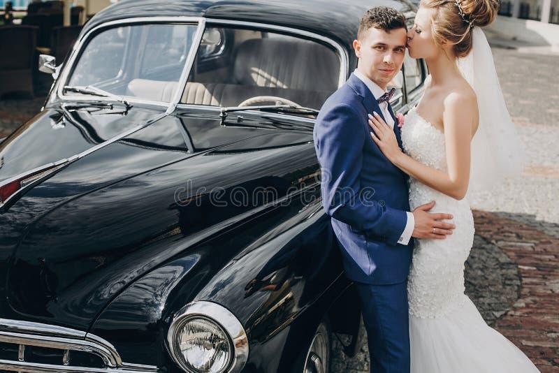 Jeunes mariés heureux élégants embrassant à la vieille rétro voiture noire Couples les épousant magnifiques des nouveaux mariés e photographie stock