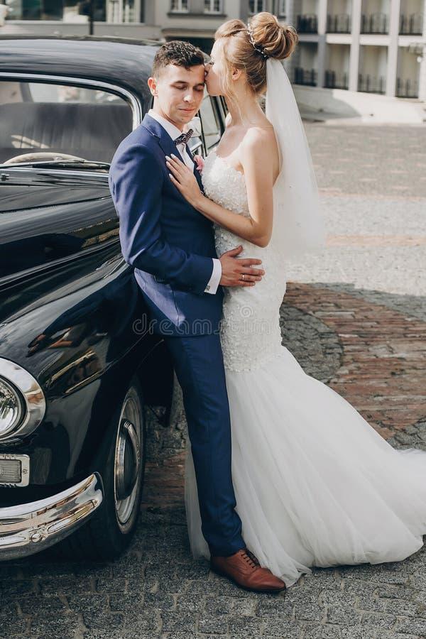 Jeunes mariés heureux élégants embrassant à la vieille rétro voiture noire Couples les épousant magnifiques des nouveaux mariés e photographie stock libre de droits