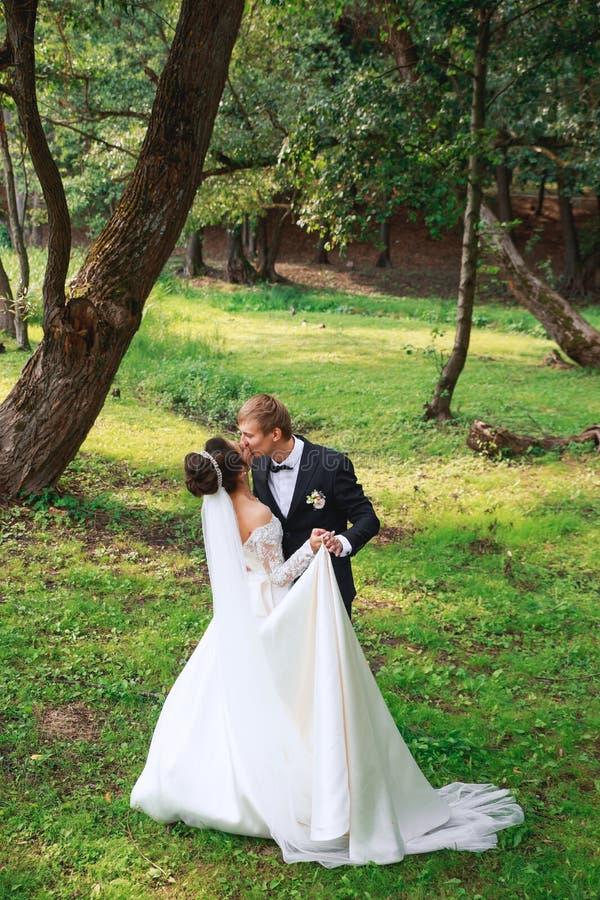 Jeunes mariés heureux après la cérémonie de mariage étreignant et embrassant photographie stock libre de droits